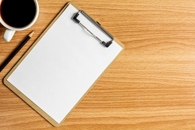 Bloco de notas em branco e um lápis na mesa de madeira.