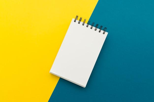 Bloco de notas em branco em fundo amarelo e azul
