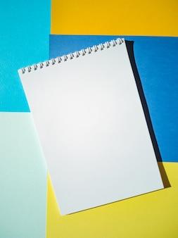 Bloco de notas em branco em uma espiral com páginas brancas em folhas de papel coloridas. vista superior, minimalismo, plana leigos.