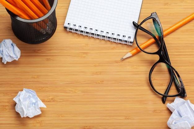 Bloco de notas em branco em uma mesa de madeira. em torno dos blocos de notas encontra-se muito papel amassado