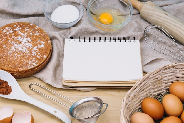 Bloco de notas em branco espiral com ingredientes e ferramentas para fazer bolo