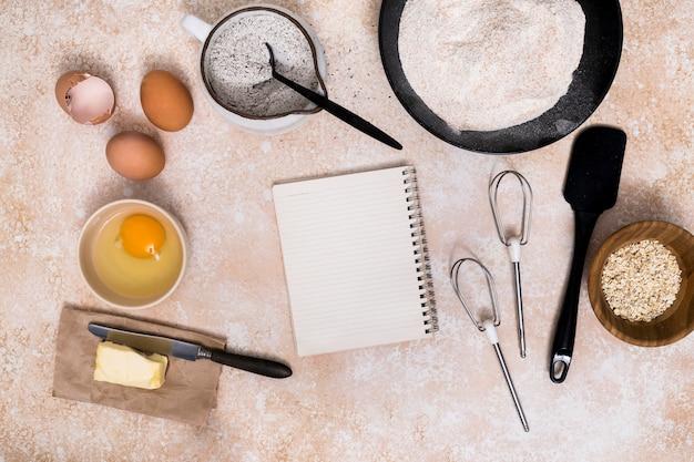Bloco de notas em branco espiral com ingredientes pão no plano de fundo texturizado