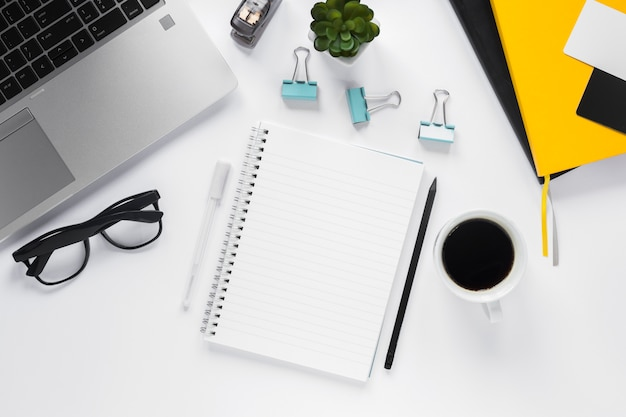 Bloco de notas em branco espiral com xícara de café e material de escritório na mesa branca