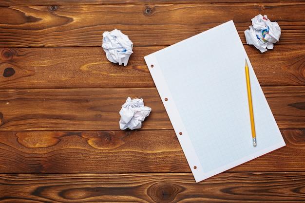 Bloco de notas em branco, lápis sobre a mesa de madeira.
