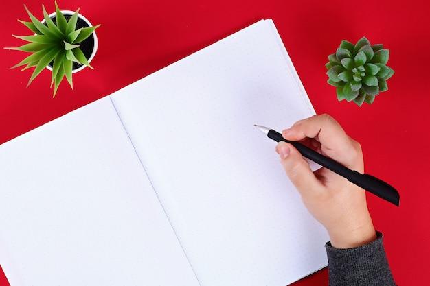 Bloco de notas em branco na mesa vermelha