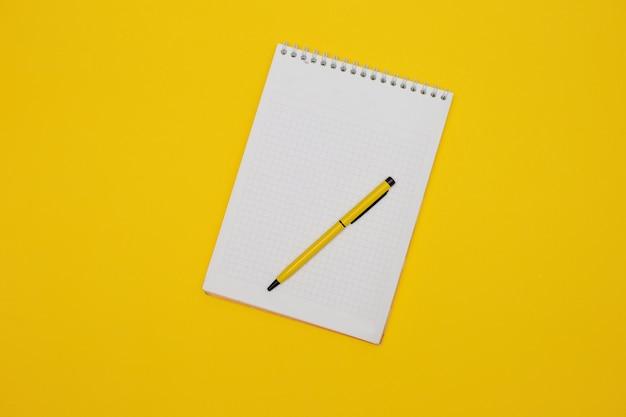 Bloco de notas em branco no amarelo com caneta amarela.