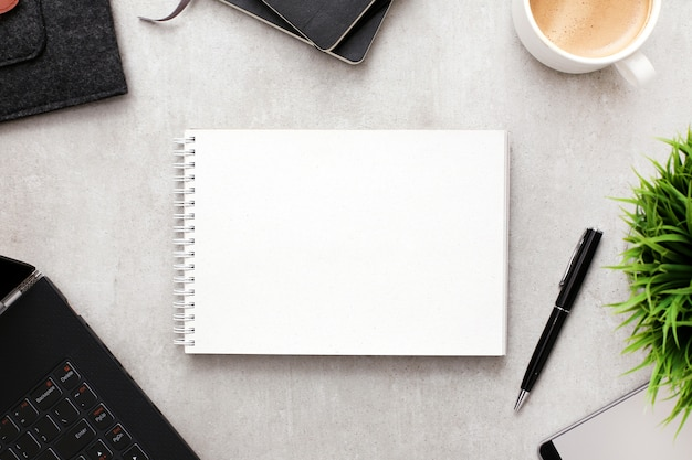 Bloco de notas em branco ou notebook no espaço de trabalho com material de escritório, vista superior
