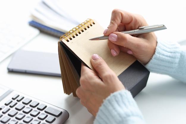 Bloco de notas em branco para escrever o planejamento do dia na mão feminina com caneta. conceito do dia de planejamento