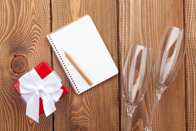 Bloco de notas em branco para espaço de cópia, caixa de presente de dia dos namorados e duas taças de champanhe sobre fundo de madeira