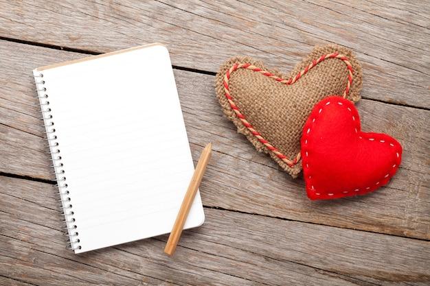 Bloco de notas em branco para espaço de cópia e corações de brinquedo vintage feitos à mão para o dia dos namorados sobre fundo de madeira