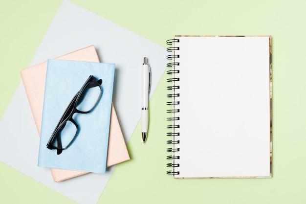 Bloco de notas em branco plana leigos sobre fundo verde claro