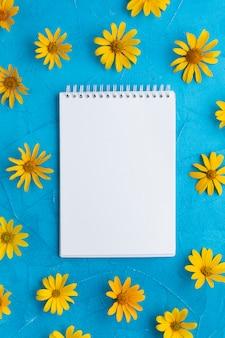 Bloco de notas em branco, rodeado por flores de ostra espanhol