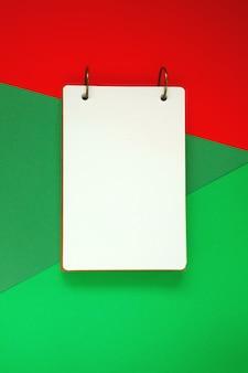 Bloco de notas em branco sobre fundo brilhante verde vermelho. caderno sobre fundo gráfico de tendência. configuração plana, vista superior, cópia espaço