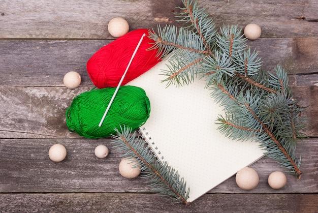 Bloco de notas em branco vazio com um padrão de bolinhas, fio, gancho, contas de madeira e ramos de abeto em uma mesa de madeira