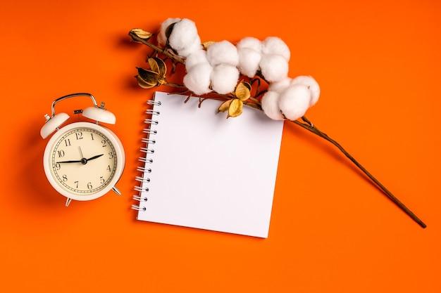 Bloco de notas em branco vazio para escrever em fundo laranja e despertador. o conceito de planejamento