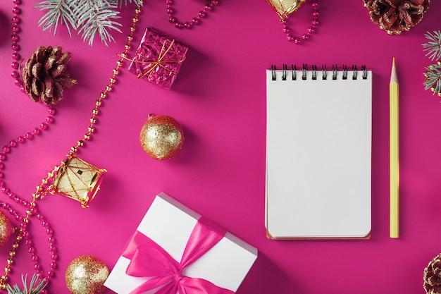 Bloco de notas em brinquedos de férias e decorações na mesa de natal rosa. o conceito de época de ano novo. a vista do topo