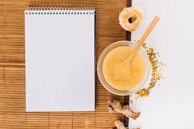 Bloco de notas em espiral; coalhada de limão; pólen de abelha; donut e gengibre no placemat