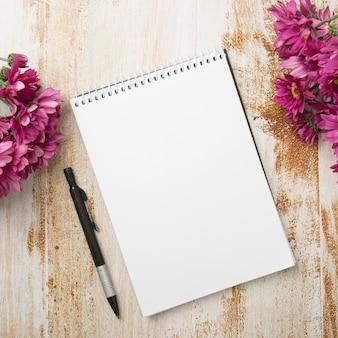 Bloco de notas em espiral com caneta e flores cor de rosa no plano de fundo texturizado de madeira