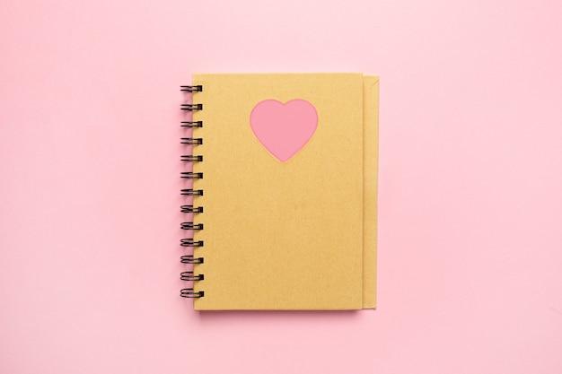 Bloco de notas em espiral com coração rosa em papel rosa, nota de minimalismo e vista superior do dia dos namorados