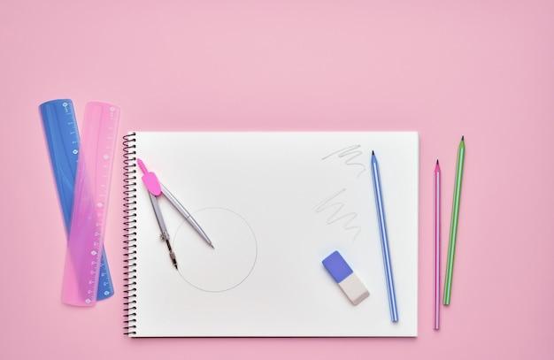 Bloco de notas em espiral com lápis em rosa pastel. volta ao conceito de escola. copie o espaço, vista superior.