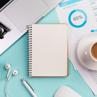 Bloco de notas em espiral fechado com laptop, fone de ouvido, caneta, mouse e xícara de café no plano de orçamento na mesa azul