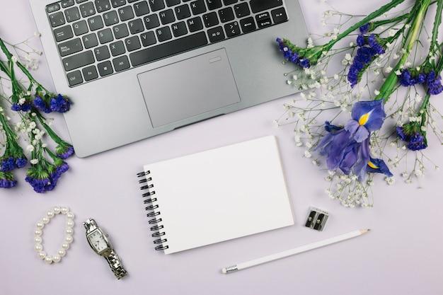 Bloco de notas em espiral; lápis; relógio de pulso; pulseira e flores roxas com laptop no fundo branco