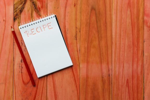 Bloco de notas em espiral perto de palavra receita perto de lápis em fundo de madeira