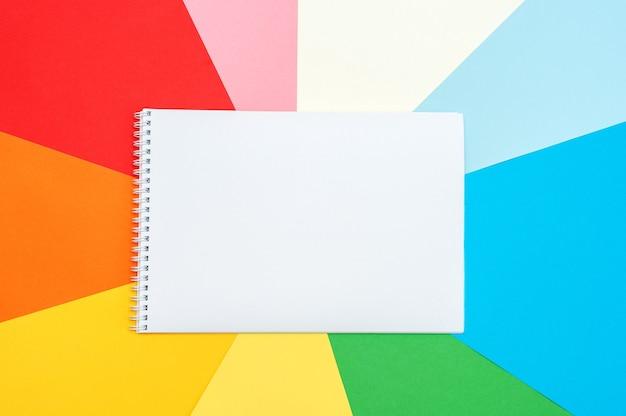 Bloco de notas em um fundo colorido. escrever uma lista ou planos. copie o espaço para seu texto.