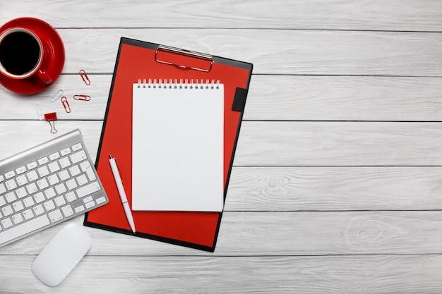 Bloco de notas em um tablet vermelho e uma mesa cinza com um mouse e teclado
