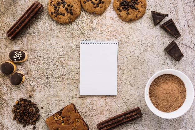 Bloco de notas entre grãos de café, biscoitos e chocolates