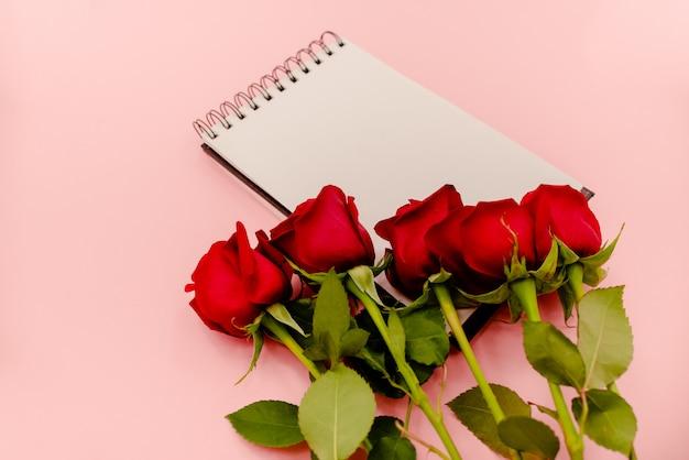 Bloco de notas espiral branco com as rosas vermelhas na luz - fundo cor-de-rosa.