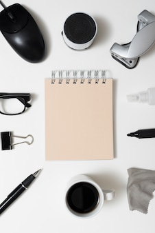 Bloco de notas espiral cercado por artigos de papelaria do escritório; xícara de café e óculos mais isolado no fundo branco
