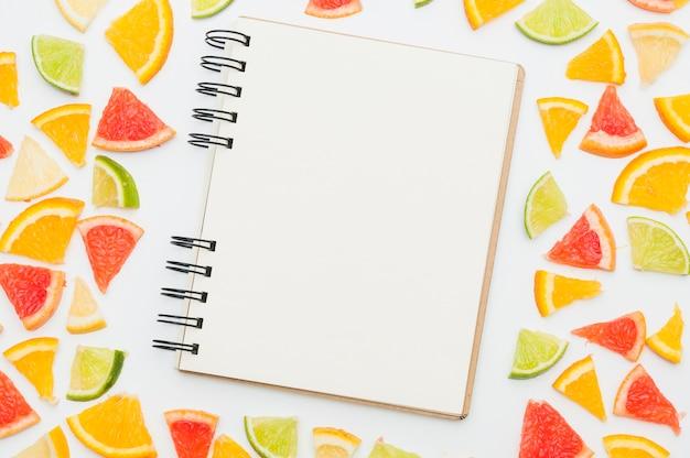 Bloco de notas espiral em branco cercado com fatias de frutas cítricas em pano de fundo branco