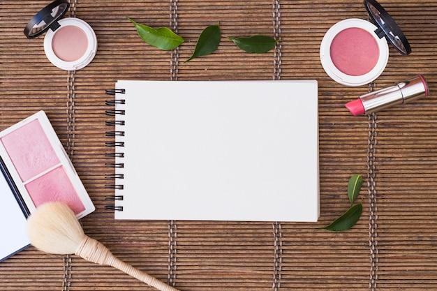 Bloco de notas espiral em branco cercado com produtos cosméticos em placemat