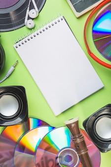 Bloco de notas espiral em branco com alto-falante; disco compacto; bloco flauta e fone de ouvido no pano de fundo verde