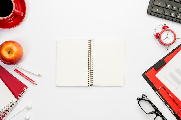 Bloco de notas espiral em branco com artigos de papelaria na mesa de escritório