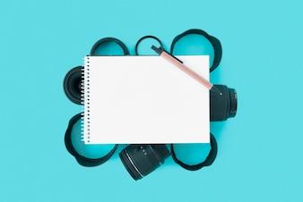 Bloco de notas espiral em branco com caneta sobre acessórios de câmera em fundo azul