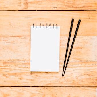 Bloco de notas espiral em branco com dois pauzinhos de madeira sobre a mesa de madeira