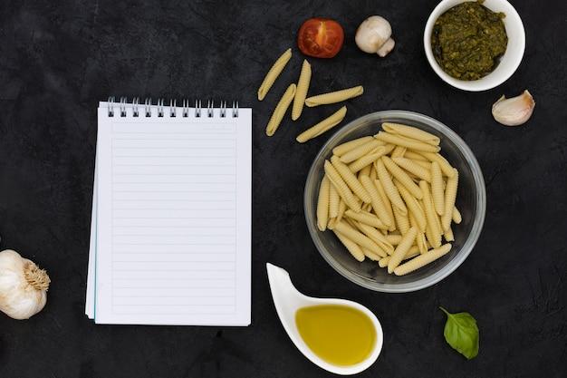 Bloco de notas espiral em branco com massas garganelli cru e ingredientes em plano de fundo texturizado preto
