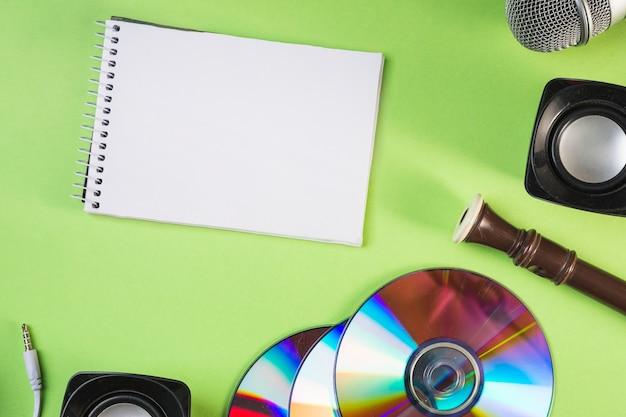 Bloco de notas espiral em branco com microfone; alto falante; disco compacto; flauta de bloco em pano de fundo verde