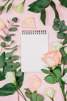 Bloco de notas espiral em branco com rosa e eustoma flores contra fundo rosa