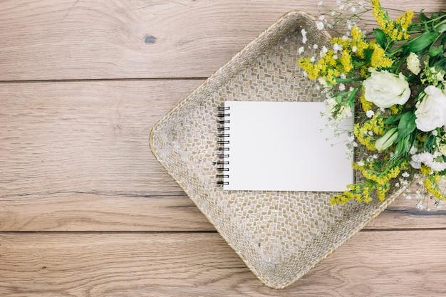 Bloco de notas espiral em branco e buquê de flores frescas na cesta na mesa de madeira