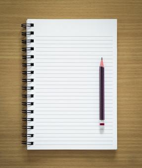 Bloco de notas espiral em branco e lápis em fundo de madeira