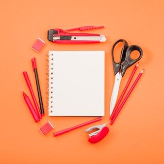 Bloco de notas espiral em branco e tesoura com artigos de papelaria sobre fundo laranja brilhante