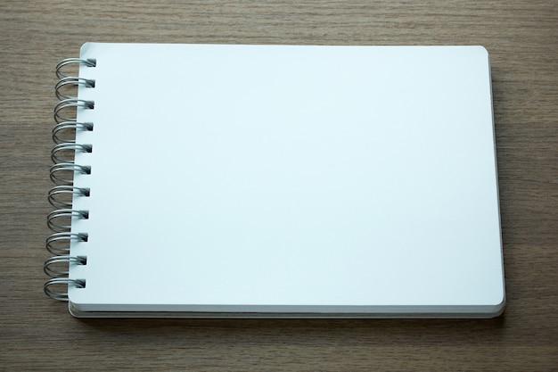 Bloco de notas espiral em branco em fundo de madeira escura