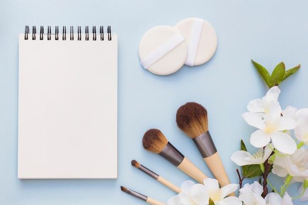 Bloco de notas espiral em branco; esponja e pincel de maquiagem com flores brancas sobre fundo azul