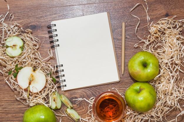 Bloco de notas espiral em branco; lápis e maçã verde com vinagre de maçã na mesa de madeira