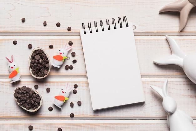 Bloco de notas espiral em branco; ovos de páscoa com chips de chocolate e coelhos em pano de fundo de madeira