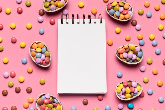 Bloco de notas espiral em branco, rodeado com doces coloridos gem no pano de fundo rosa