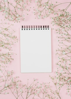 Bloco de notas espiral em branco, rodeado de flores gypsophila contra fundo rosa